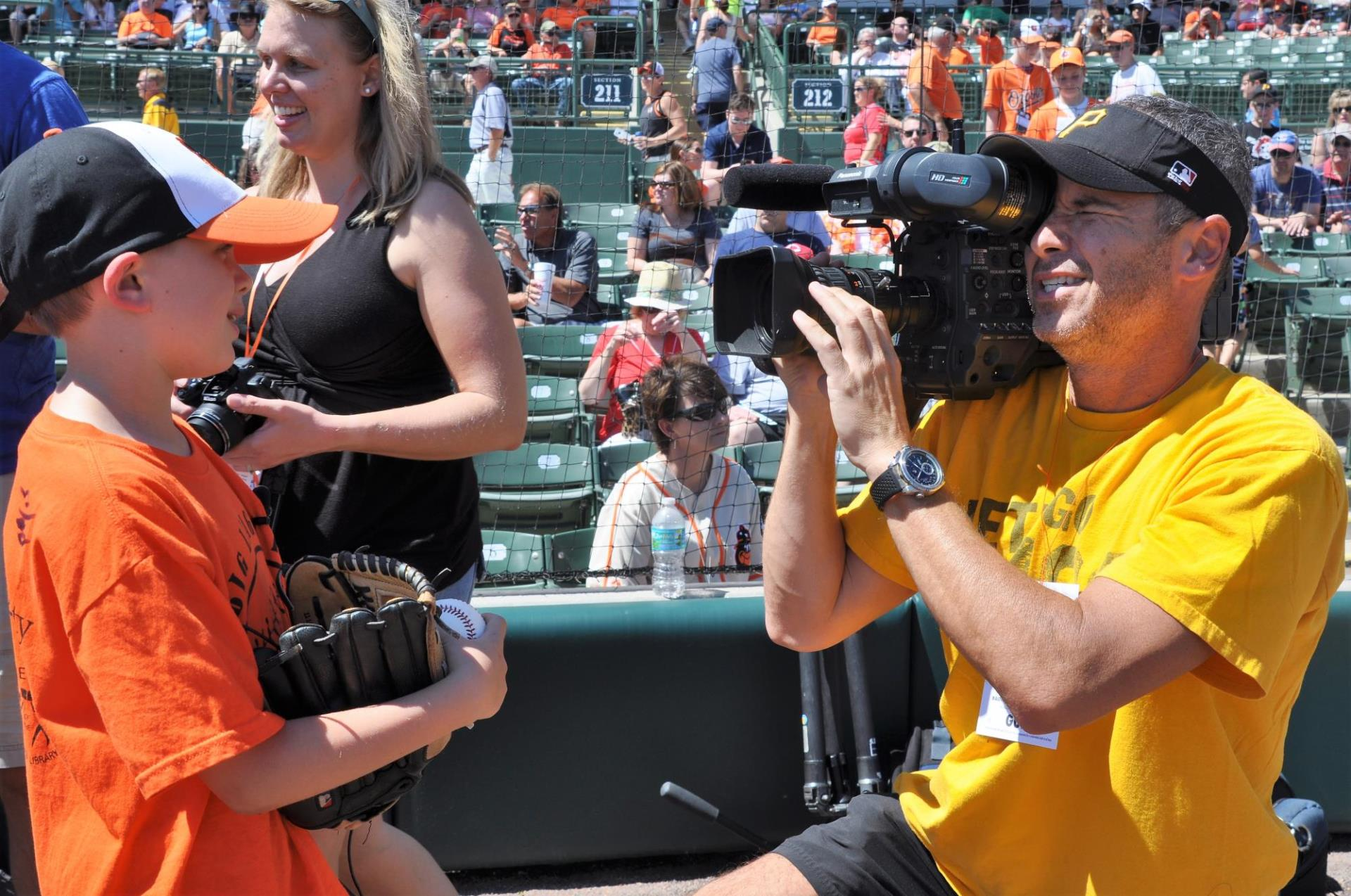 Videographer shooting an interview with a child at Ed Smith Stadium in Sarasota