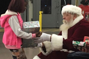 Santa Clause handing out gift to child