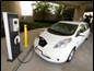 Electric car plugged into public charging station