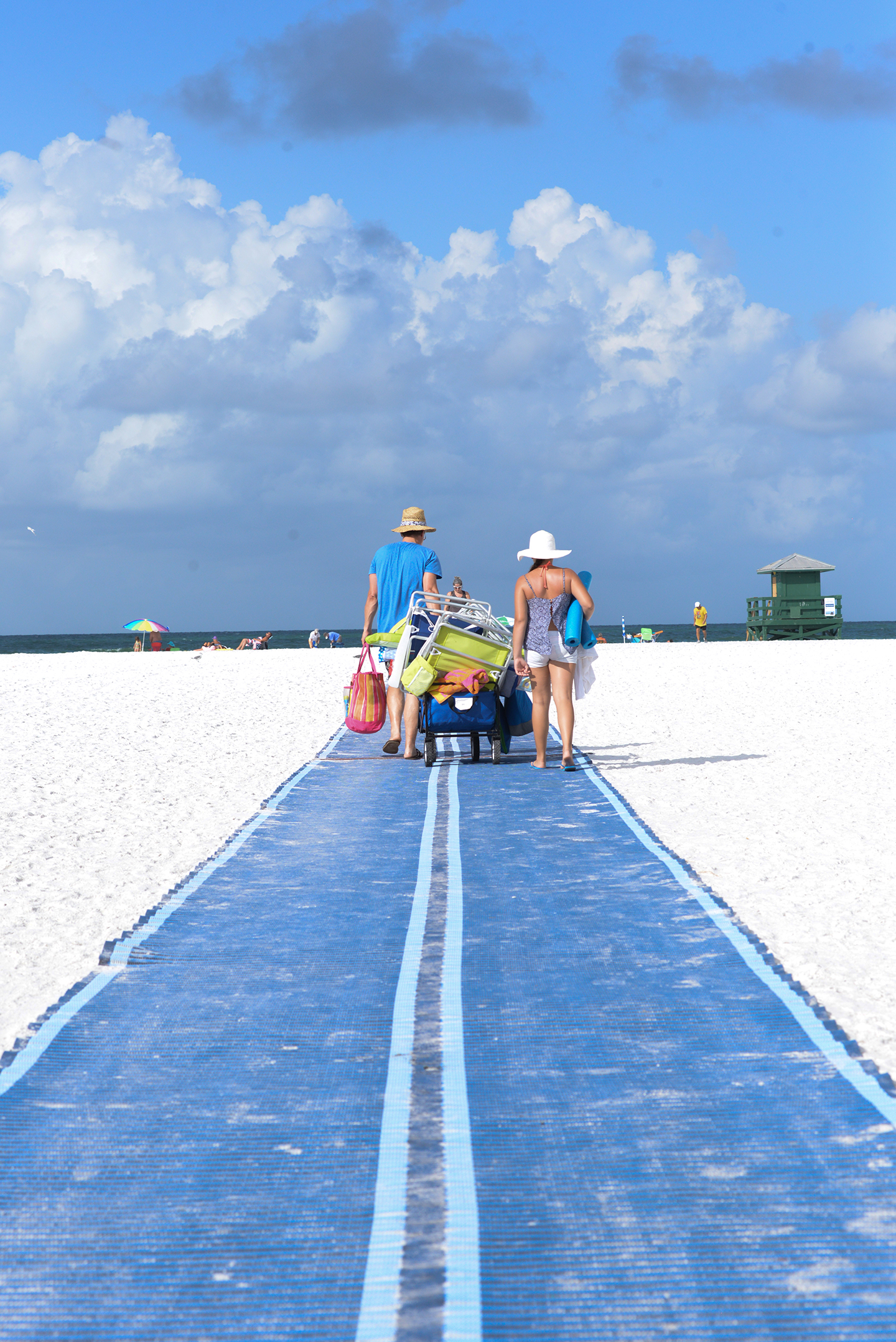 Couple using the new Mobi Mat to pull a wagon onto Siesta Beach