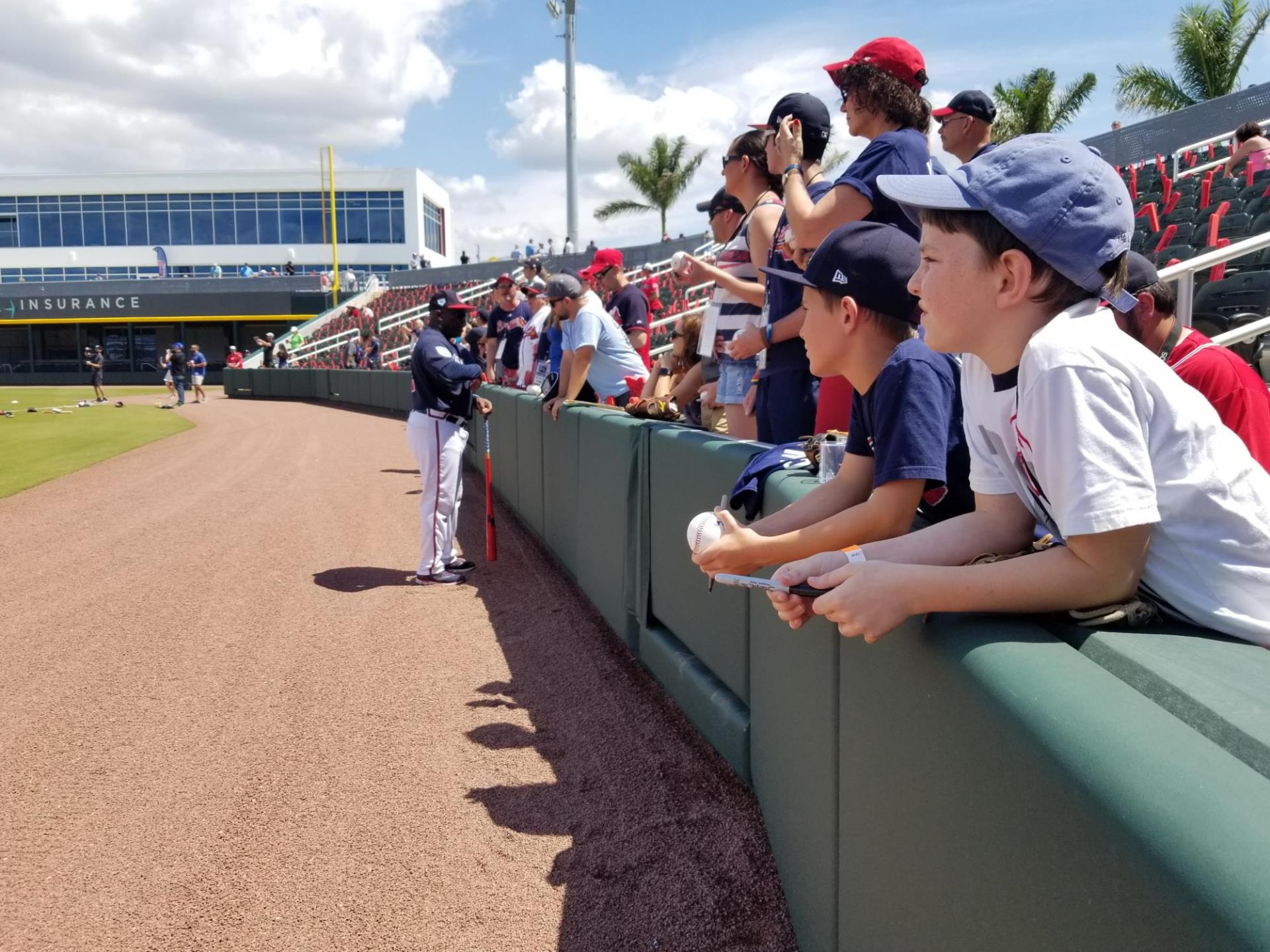Baseball fans of all ages line up along first base line in hopes of getting major league signatures before the Braves first game in their new spring training facility in Sarasota County.