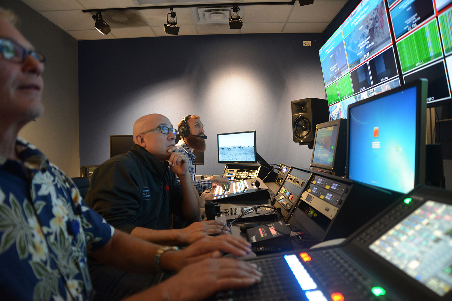 Three television technicians operating equipment in the Access Sarasota television production control room