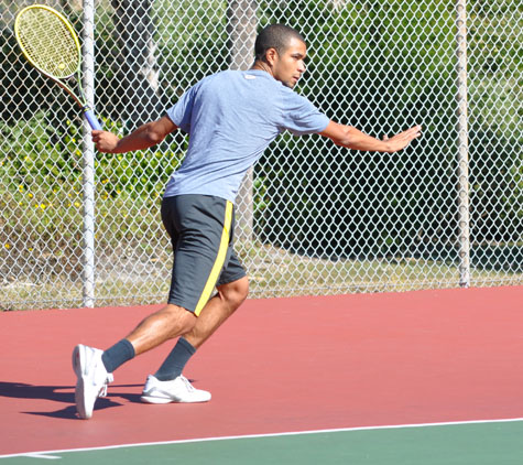 Man playing tennis, about to hit the ball
