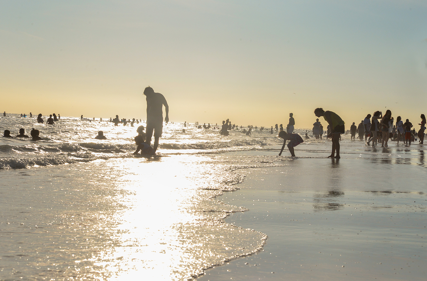 People on Siesta Beach at twilight, playing on the shoreline