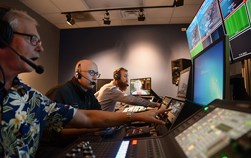 Communication staff work on the master controls for a production in the Access Sarasota studio.