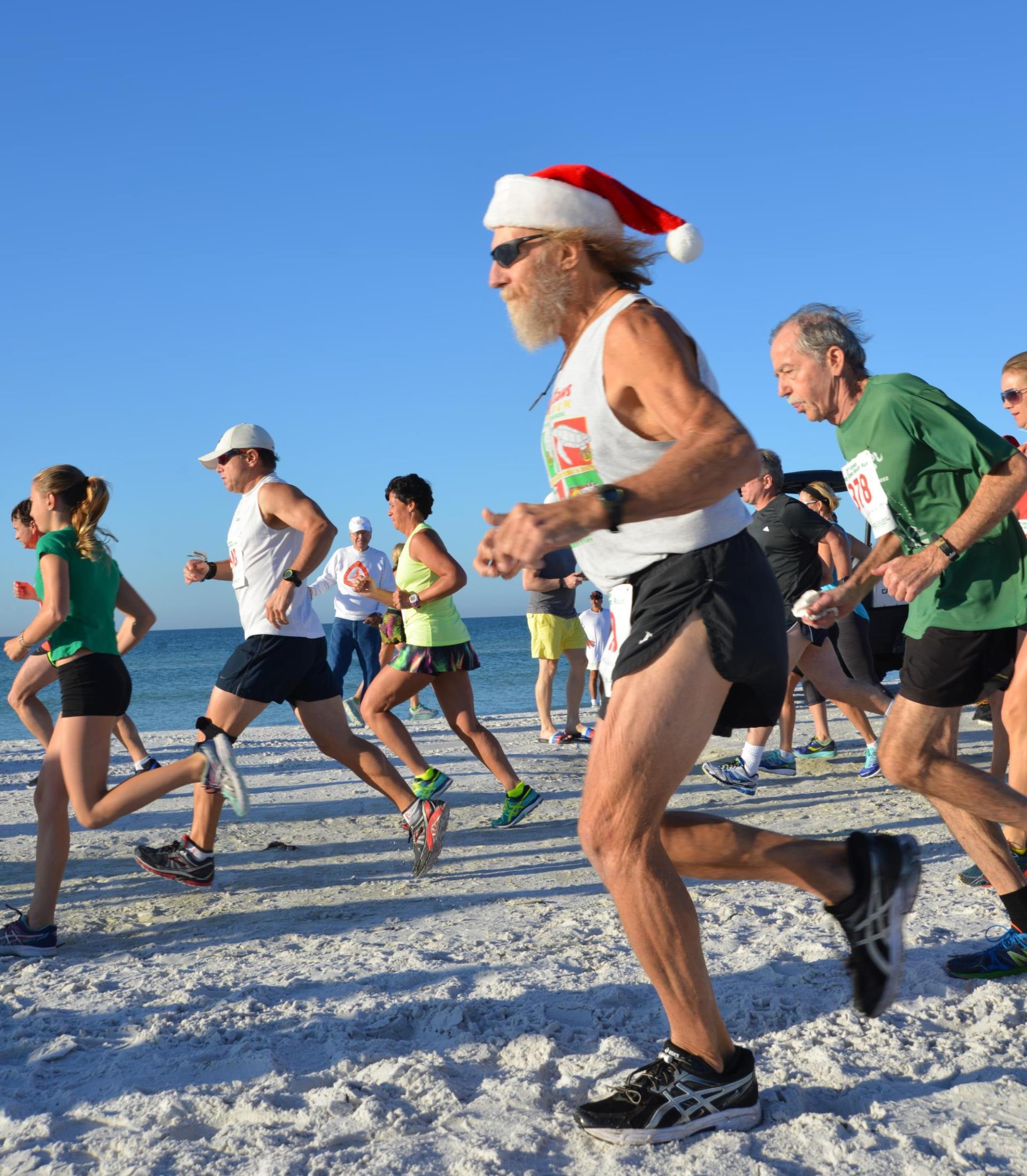 Runners enjoying the beach in December during the Sandy Claws Beach Run.